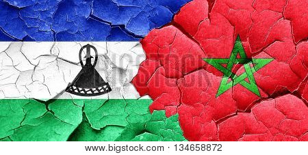 Lesotho flag with Morocco flag on a grunge cracked wall