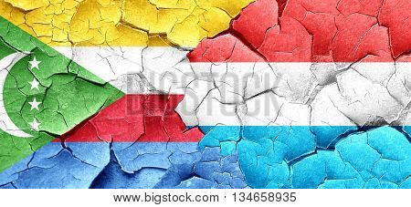Comoros flag with Luxembourg flag on a grunge cracked wall