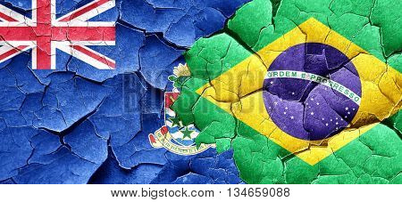 cayman islands flag with Brazil flag on a grunge cracked wall