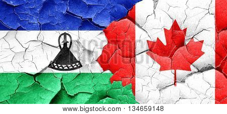 Lesotho flag with Canada flag on a grunge cracked wall