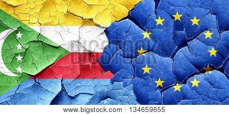 Comoros flag with european union flag on a grunge cracked wall