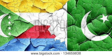 Comoros flag with Pakistan flag on a grunge cracked wall