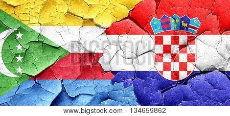 Comoros flag with Croatia flag on a grunge cracked wall