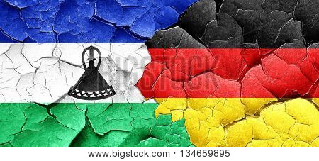 Lesotho flag with Germany flag on a grunge cracked wall