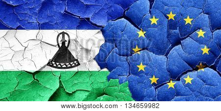 Lesotho flag with european union flag on a grunge cracked wall
