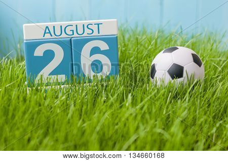 August 26th. Image of august 26 wooden color calendar on green grass lawn background with soccer ball. Summer day. Empty space for text.