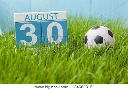 August 30th. Image of august 30 wooden color calendar on green grass lawn background with soccer ball. Summer day. Empty space for text.
