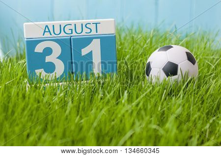 August 31st. Image of august 31 wooden color calendar on green grass lawn background with soccer ball. Summer day. Empty space for text.
