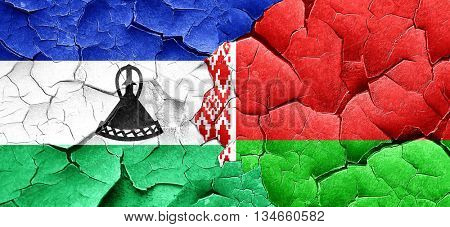 Lesotho flag with Belarus flag on a grunge cracked wall