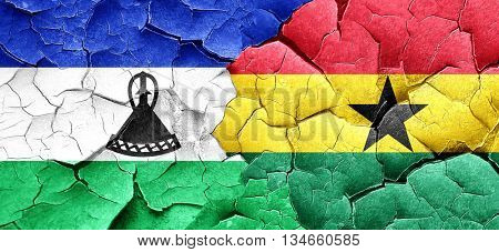 Lesotho flag with Ghana flag on a grunge cracked wall