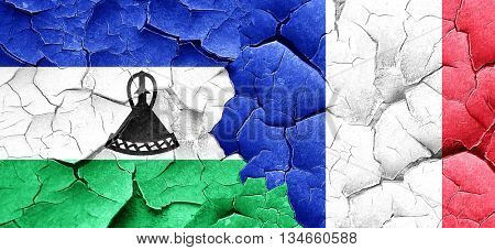 Lesotho flag with France flag on a grunge cracked wall