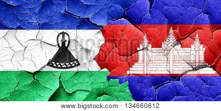 Lesotho flag with Cambodia flag on a grunge cracked wall