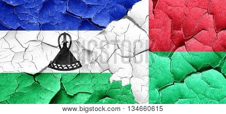 Lesotho flag with Madagascar flag on a grunge cracked wall
