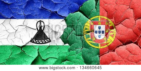 Lesotho flag with Portugal flag on a grunge cracked wall