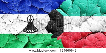 Lesotho flag with Kuwait flag on a grunge cracked wall