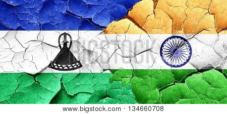 Lesotho flag with India flag on a grunge cracked wall