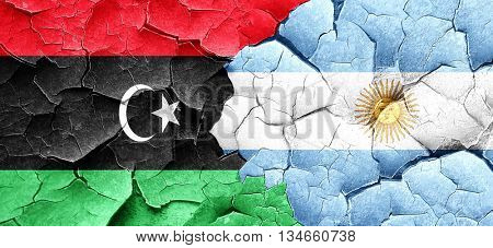 Libya flag with Argentine flag on a grunge cracked wall