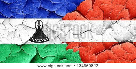 Lesotho flag with Austria flag on a grunge cracked wall