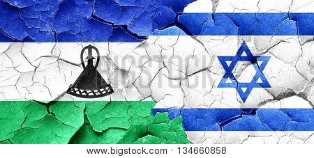 Lesotho flag with Israel flag on a grunge cracked wall