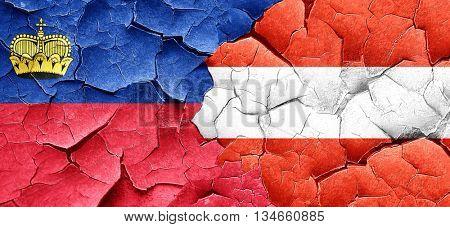 Liechtenstein flag with Austria flag on a grunge cracked wall