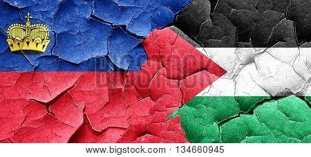 Liechtenstein flag with Palestine flag on a grunge cracked wall