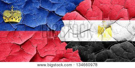 Liechtenstein flag with egypt flag on a grunge cracked wall