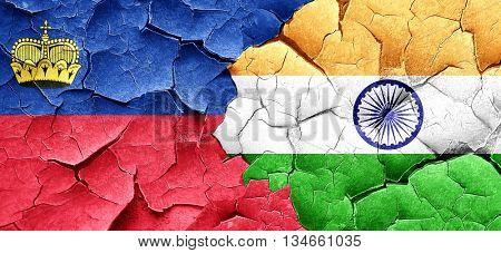 Liechtenstein flag with India flag on a grunge cracked wall