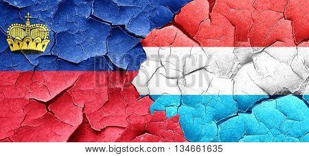 Liechtenstein flag with Luxembourg flag on a grunge cracked wall