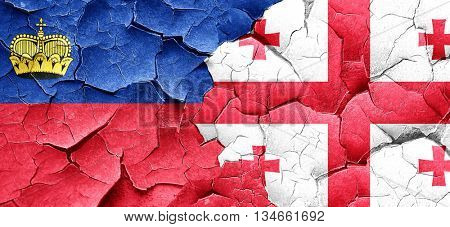 Liechtenstein flag with Georgia flag on a grunge cracked wall