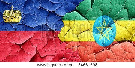 Liechtenstein flag with Ethiopia flag on a grunge cracked wall
