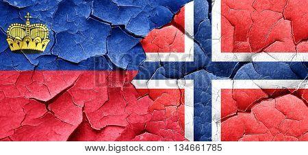 Liechtenstein flag with Norway flag on a grunge cracked wall