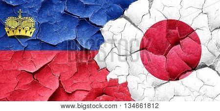 Liechtenstein flag with Japan flag on a grunge cracked wall