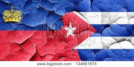 Liechtenstein flag with cuba flag on a grunge cracked wall
