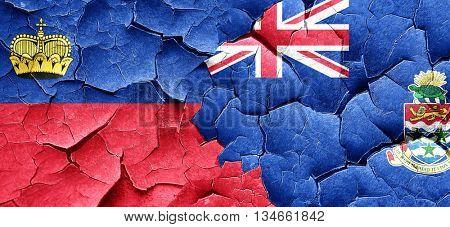 Liechtenstein flag with Cayman islands flag on a grunge cracked