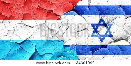 Luxembourg flag with Israel flag on a grunge cracked wall