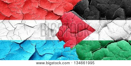 Luxembourg flag with Palestine flag on a grunge cracked wall