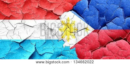 Luxembourg flag with Philippines flag on a grunge cracked wall