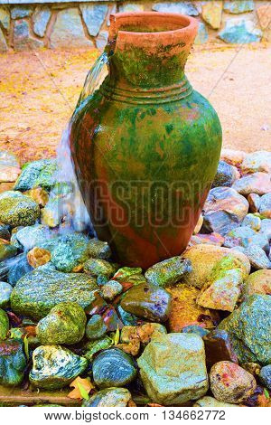 Water fountain sculpture with running water amongst rocks taken in a residential garden