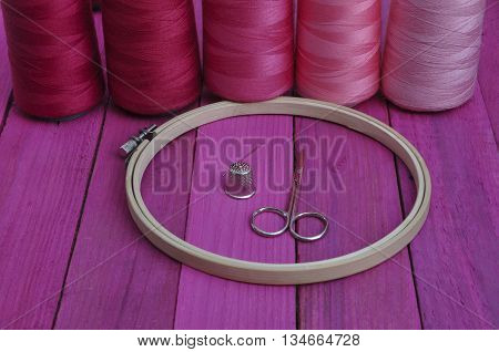 Several of red thread reel in a wooden embroidery frame on the pink table