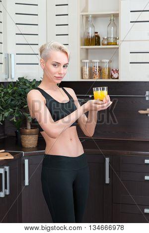 thin woman holding orange juice in modern kitchen