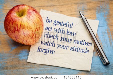 be grateful and other inspirational phrases - handwriting on a napkin with a fresh apple