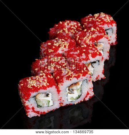 Sushi rolls with soft cheese eel cucumber and flying fish roe on black background
