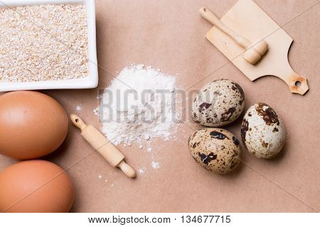 Brown-shelled and quail eggs with wooden toy culinary utensils flour groats for cooking on brown paper background