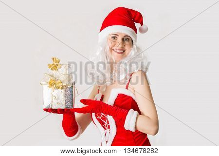Beautiful young woman in Santa Clause costume holding Xmas present. Christmas background