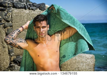Attractive young shirtless athletic man standing in water by sea or ocean shore, wearing shorts, looking at camera, with beach towel