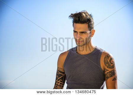 Half Body Shot of a Handsome Athletic Young Man in Trendy Attire, on a Beach in a Sunny Summer Day, Looking Away against Blue Sky Background.