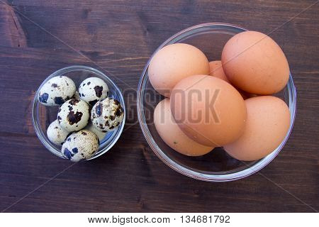 Bowls with quail eggs and chicken on a wooden table top views