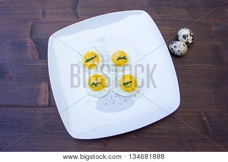Fried quail eggs on a wooden table top views