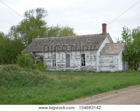 An abandoned Rural School House along side a gravel road.