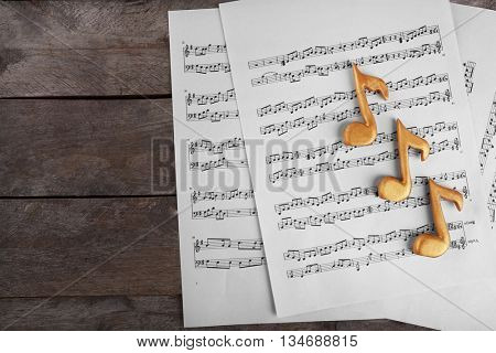 Golden music notes and sheets on wooden table, top view